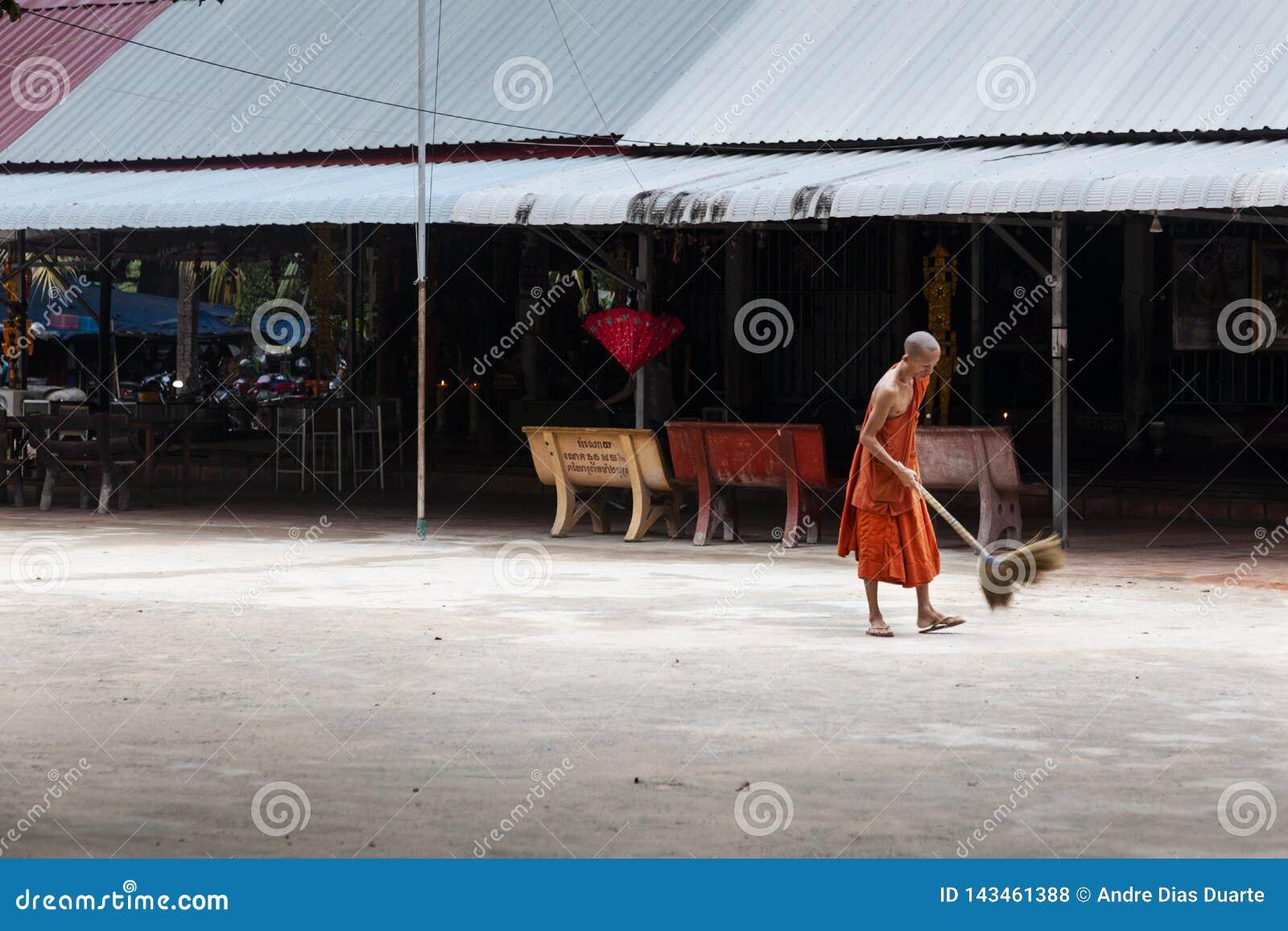 Buddistisk munk som utanför sopar golvet