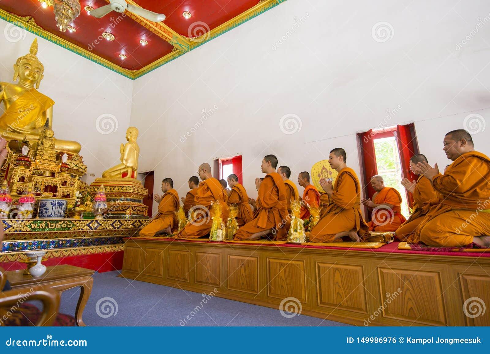 Buddistiska munkar ber på Buddhastatyn, den selektiva fokusen