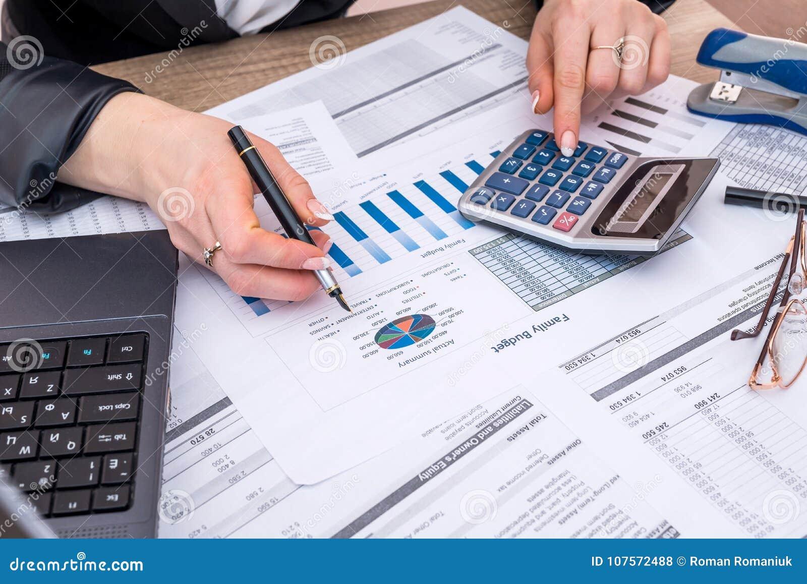 Budget annuel de compte de femme d affaires avec l ordinateur portable, stylo