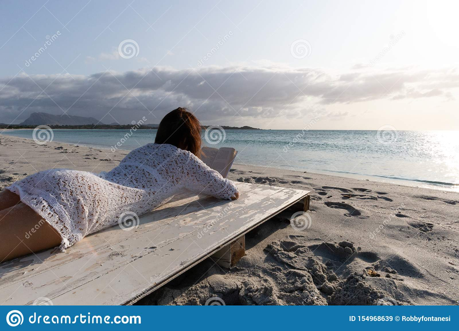Budoni, Italy - July 20 2019: young woman lying by the sea looks at the horizon at dawn in the wind dressed in a white lace dress