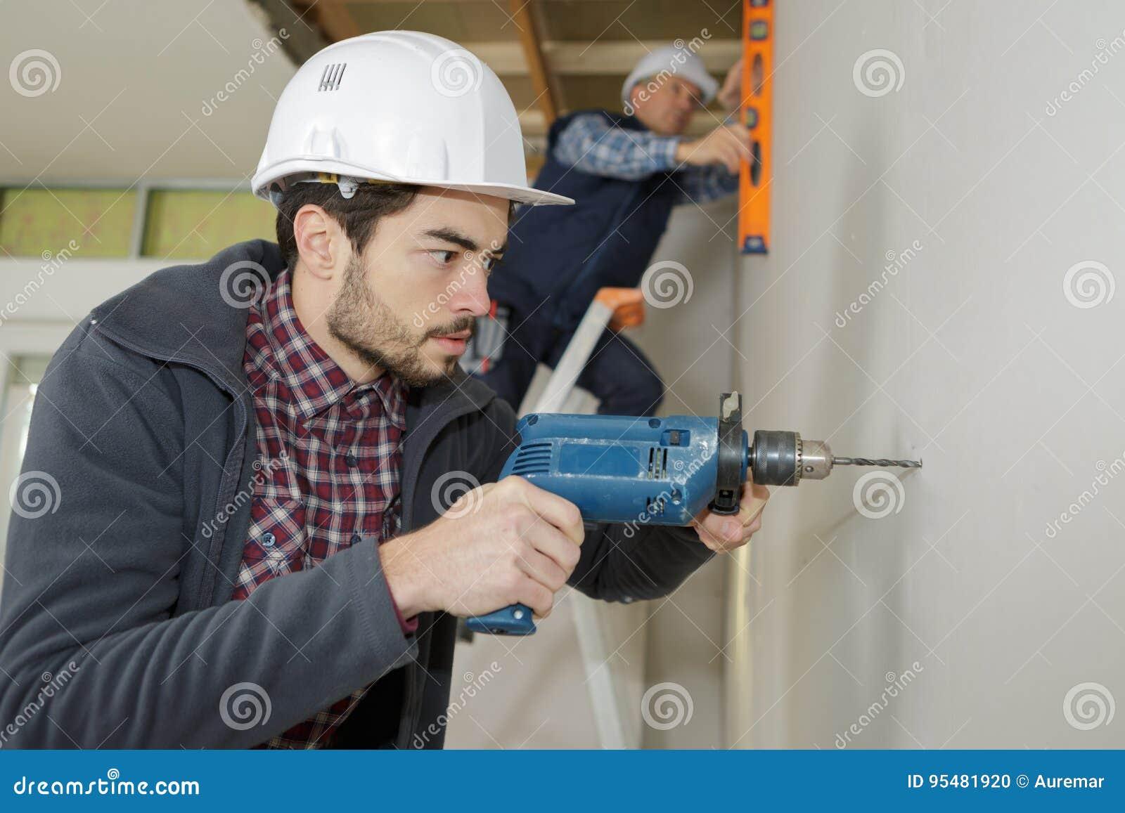 Budowa pracownicy musztruje z maszyną lub dri