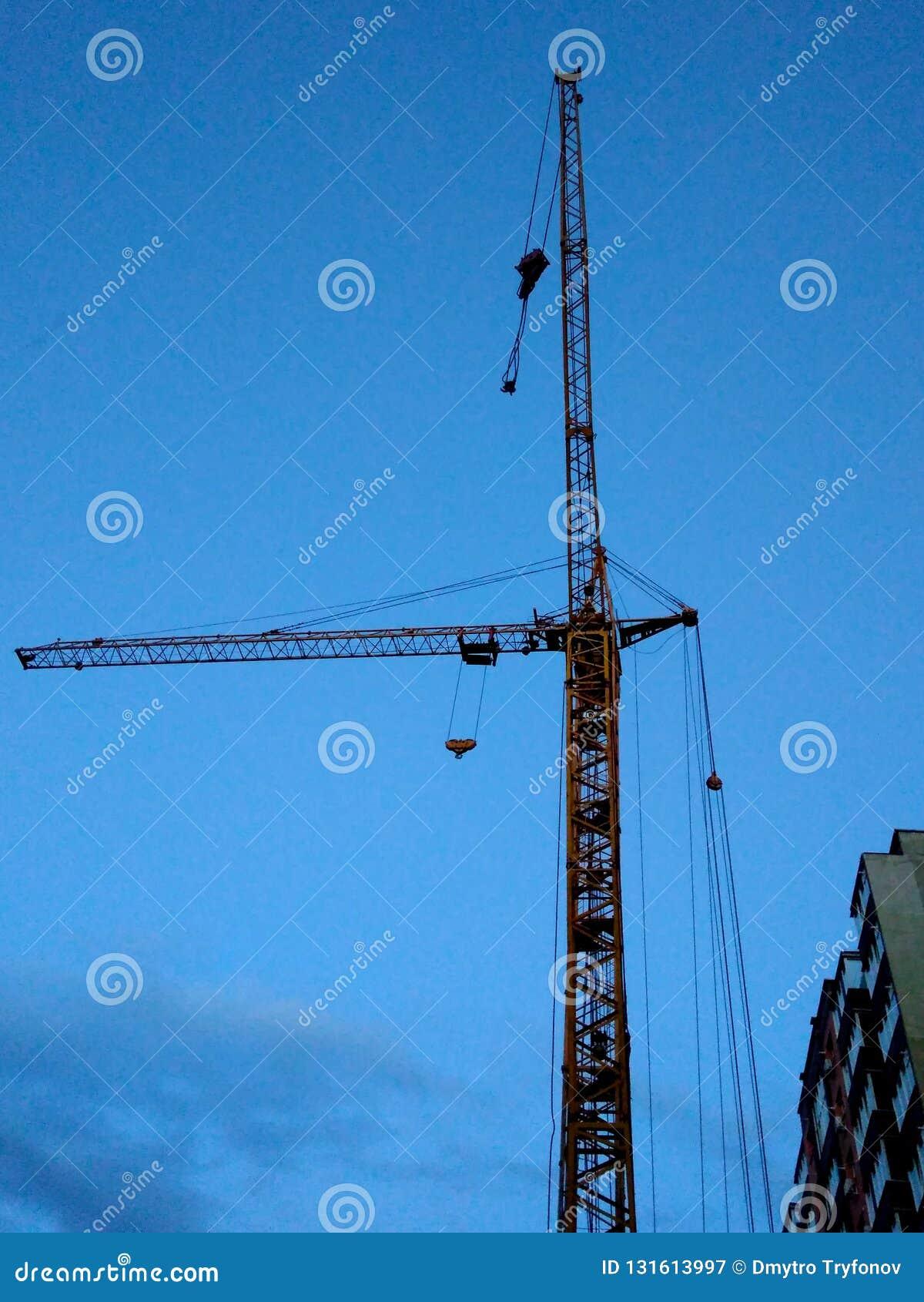 Budowa z żurawiem, remontowa praca, niebieskie niebo przy zmierzchem