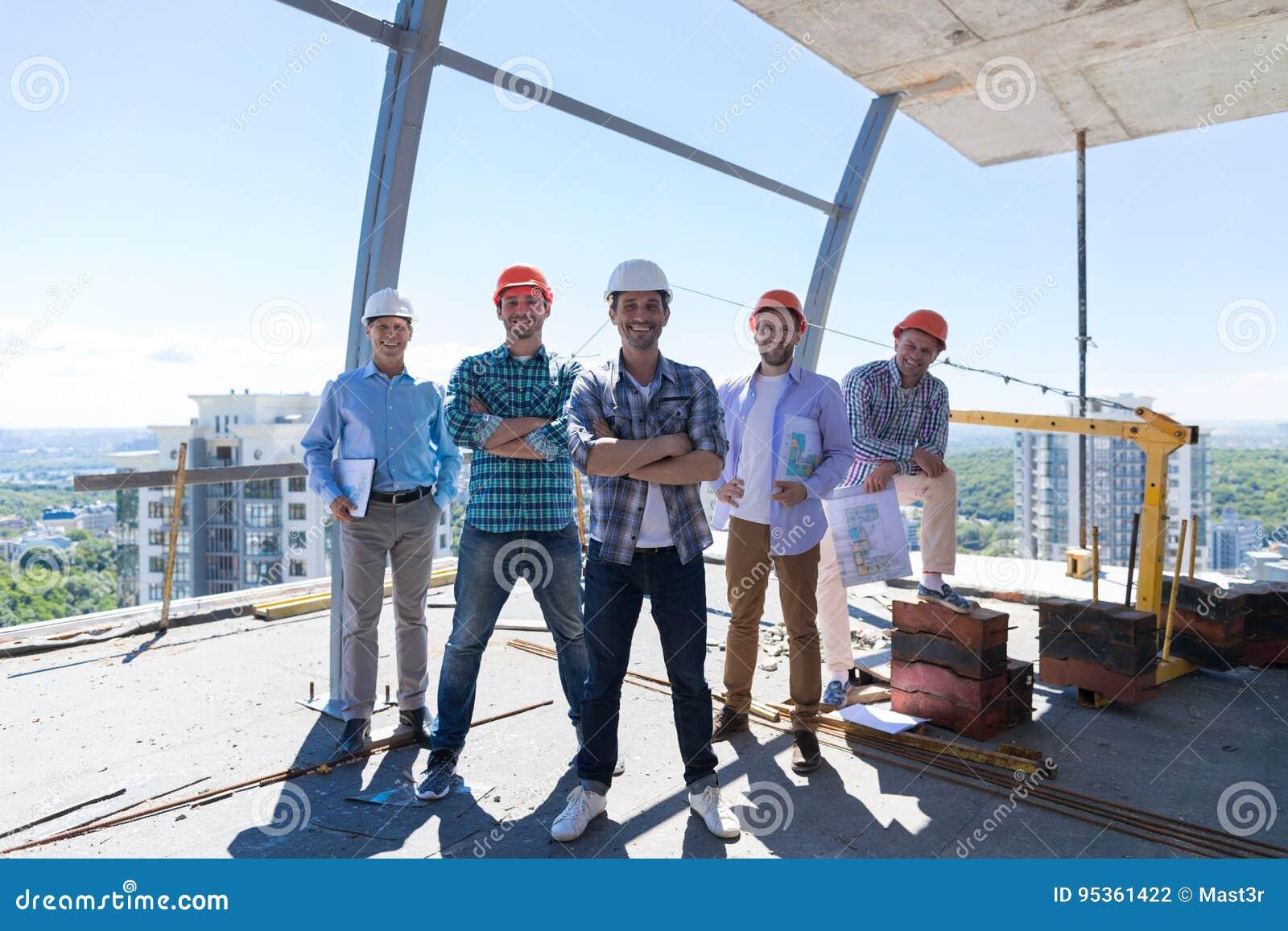 Budowniczego lider zespołu Z grupą aplikanci Przy budową Nad miasto widoku tłem, Szczęśliwi ono Uśmiecha się inżyniery