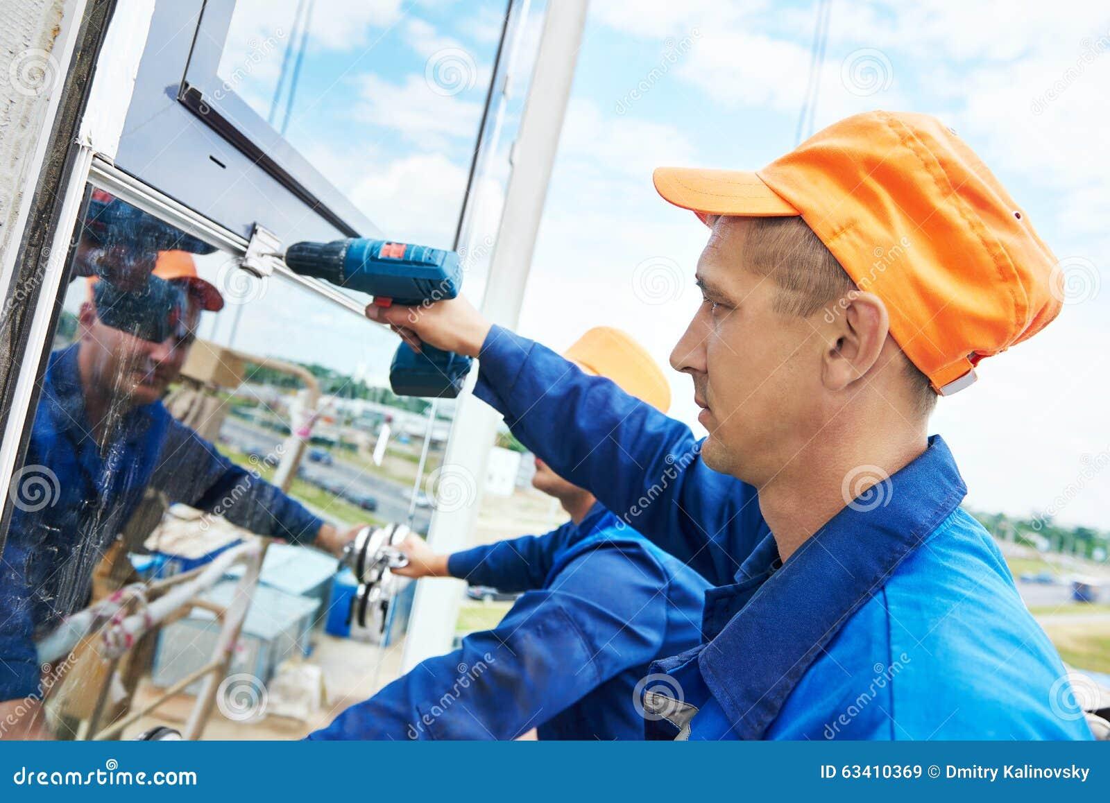 Budowniczego pracownik instaluje szklanych okno na fasadzie