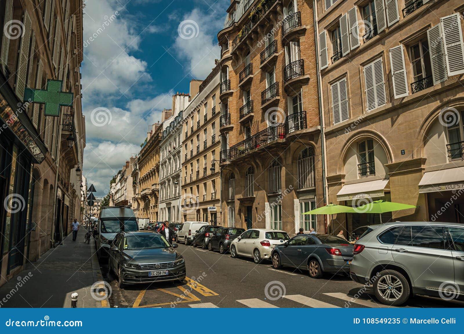 Budynki i ludzie chodzi w dół ulicę w słonecznym dniu przy Paryż