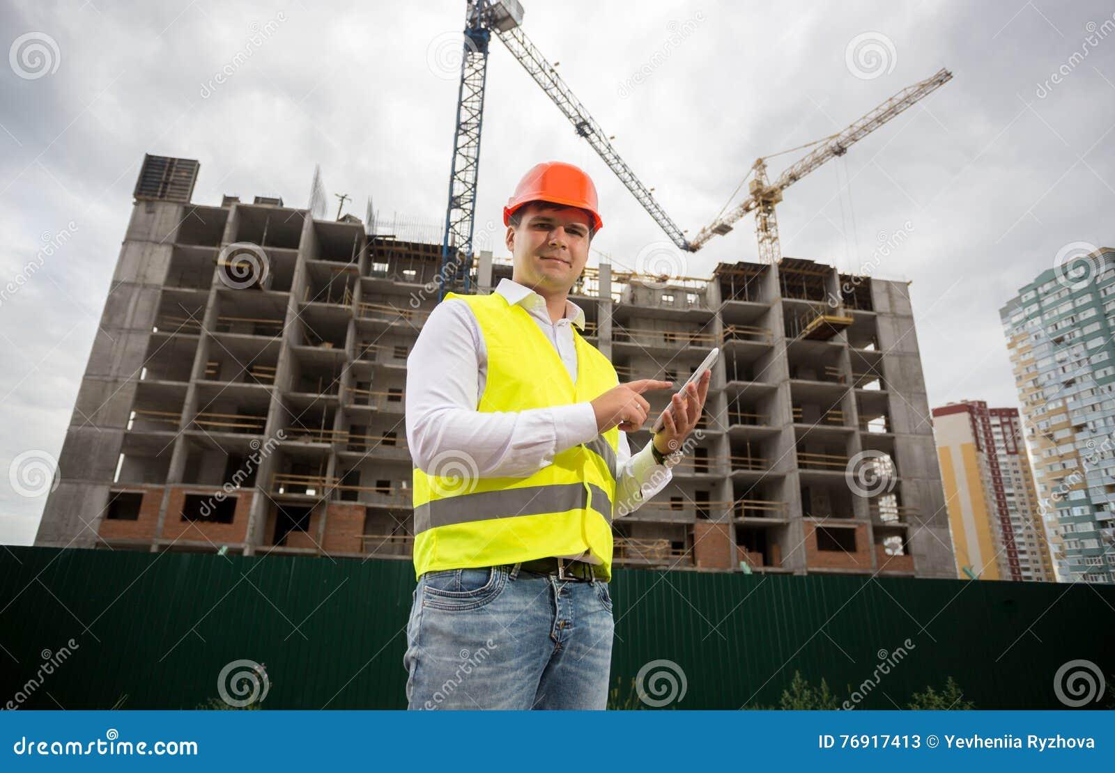 Budynku inspektor z cyfrową pastylką na budowie