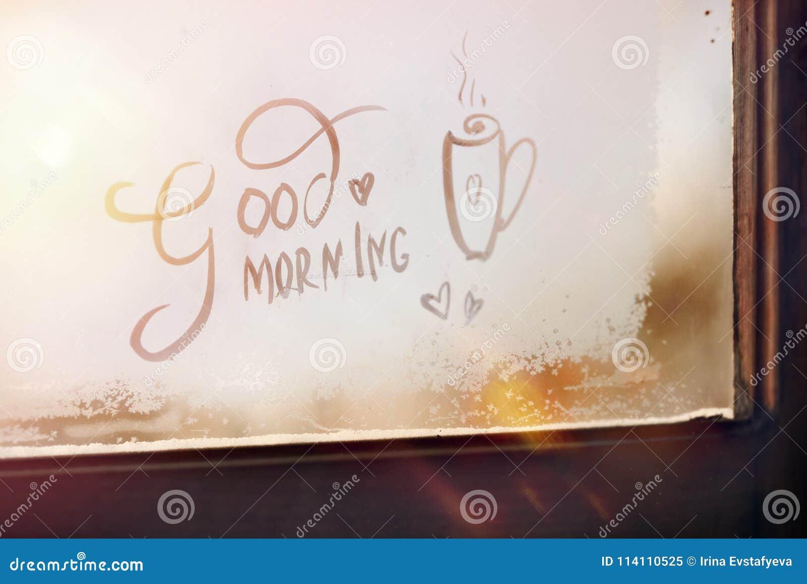 Buena mañana - la inscripción en la ventana escarchada positivo sol