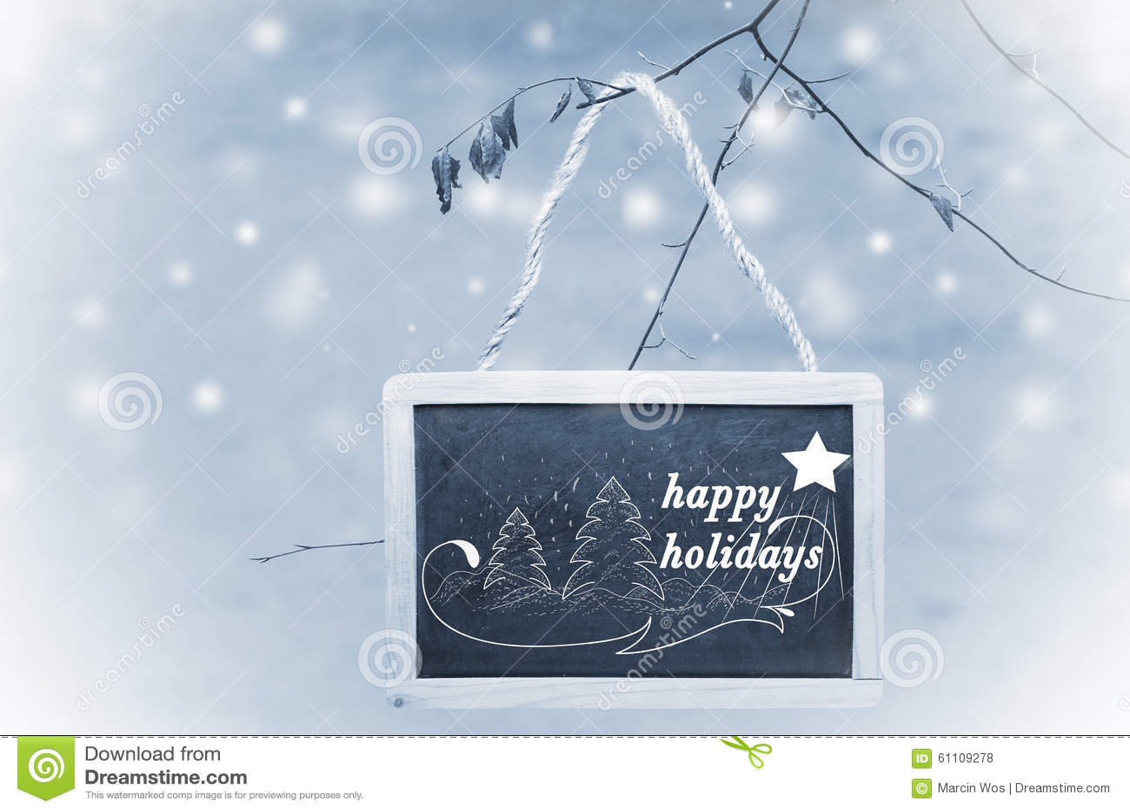 Buenas fiestas escrito en la ejecución negra del tablero de tiza de un árbol en fondo azul, nevoso Ornamento del árbol de navidad