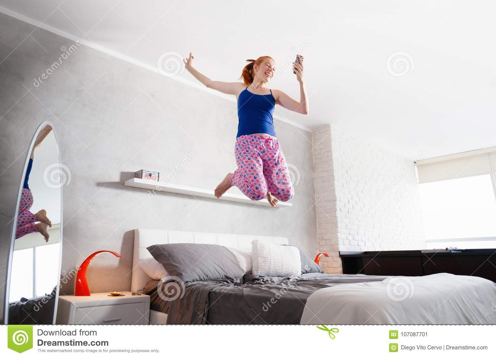 Buenas noticias para la muchacha feliz de la mujer joven que salta en cama