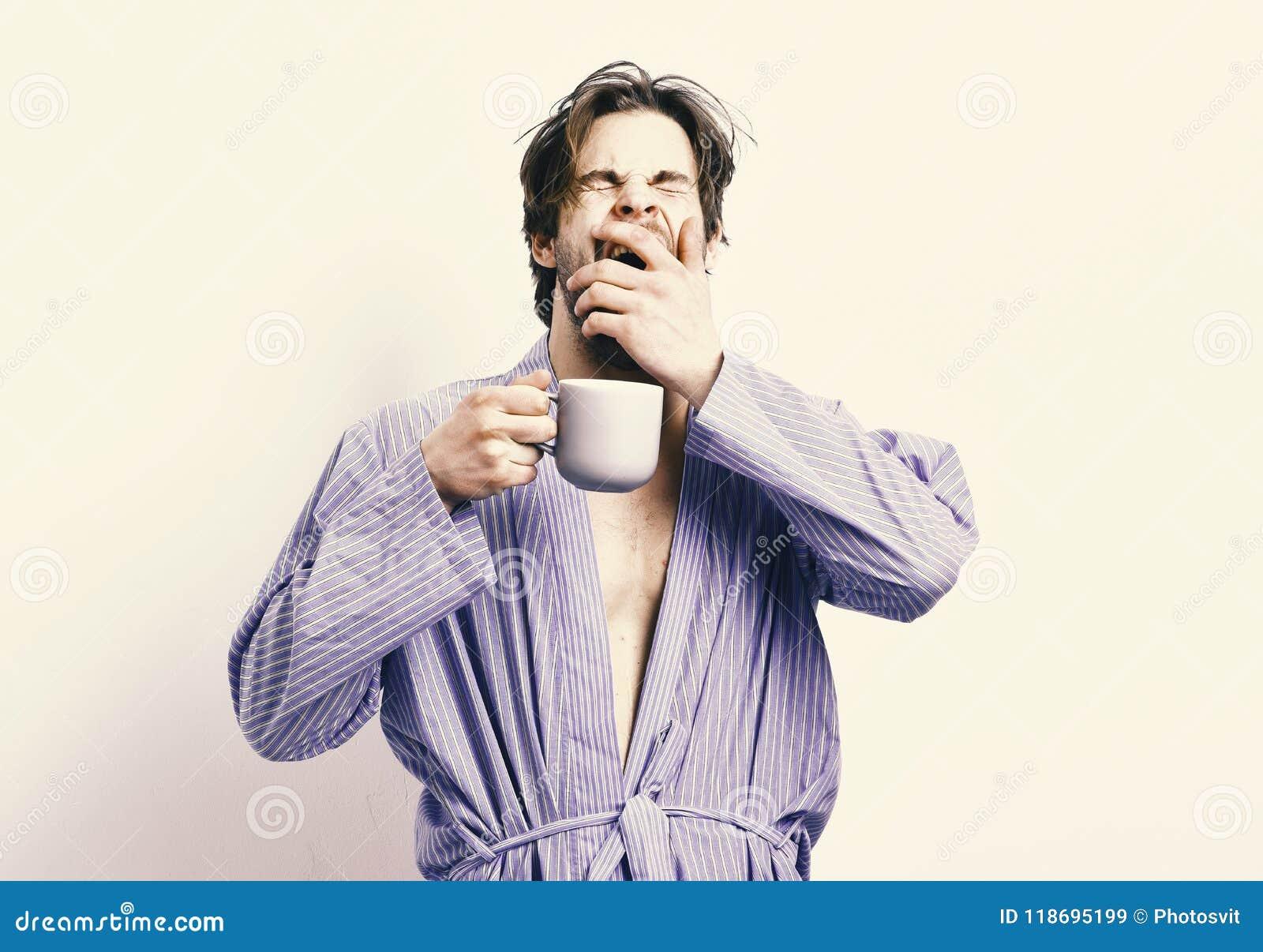 Buenos días El deportista con la cara soñolienta se coloca en albornoz con la taza