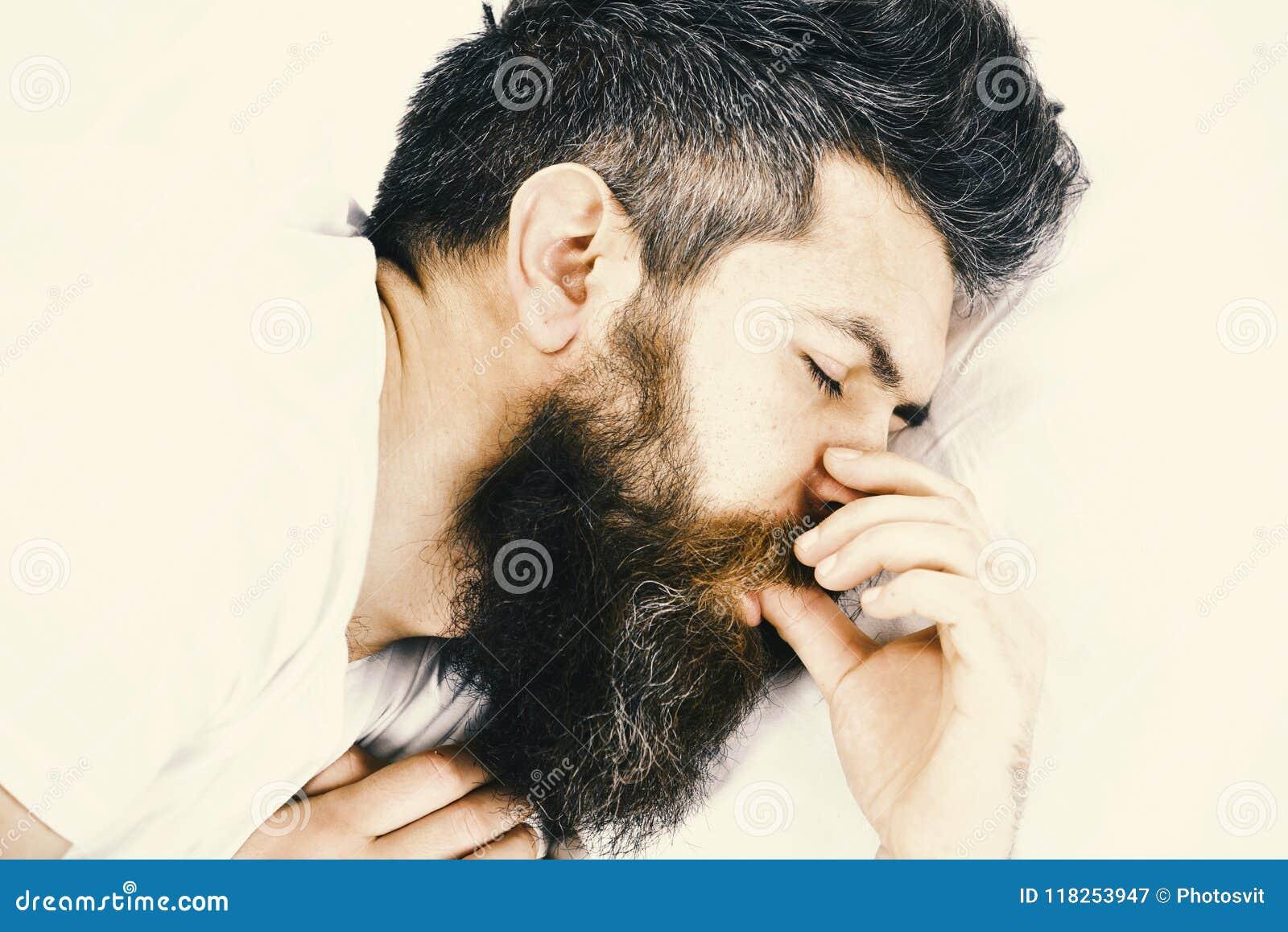 Buenos días El hombre con la cara soñolienta miente en la almohada Concepto del sueño profundo