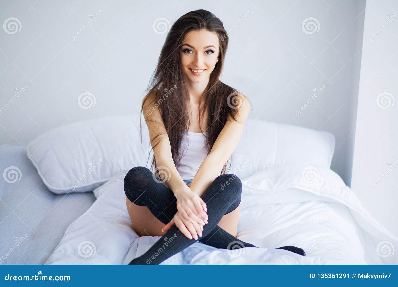 Buenos días Retrato de una sonrisa mujer morena bastante joven que se relaja en la cama blanca