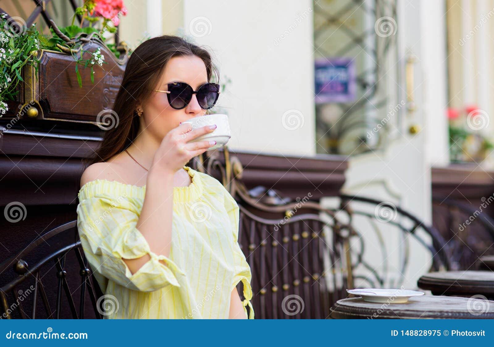 Buenos d?as Muchacha del desayuno relajarse en café Almuerzo de asunto la mujer elegante en vidrios bebe el caf? Manera del veran