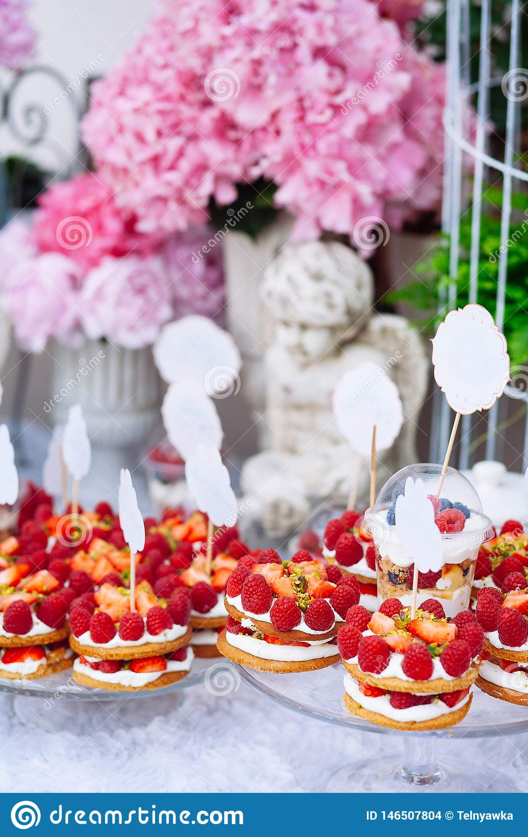 Buffet with sweets. Cakes with raspberries. Sweet table for banquets, weddings, parties