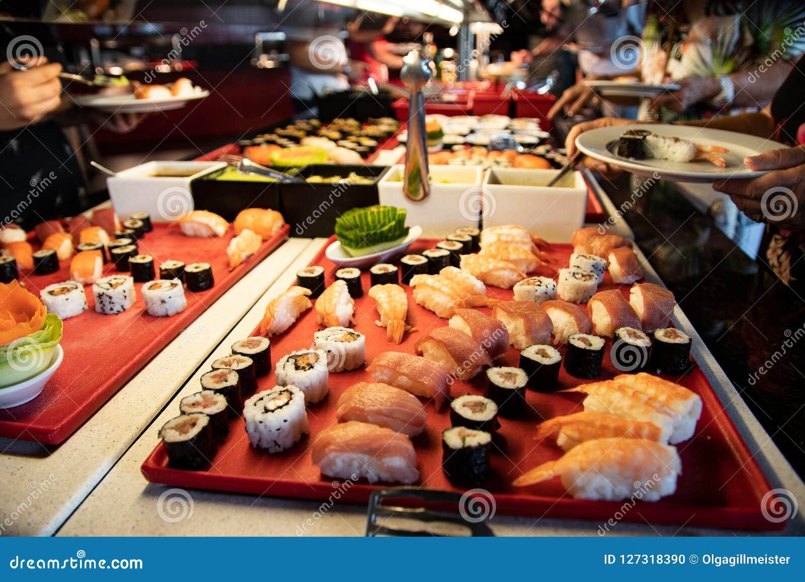 Buffett matställe Händer som upp väljer sushi- och fiskspecialiteter i b