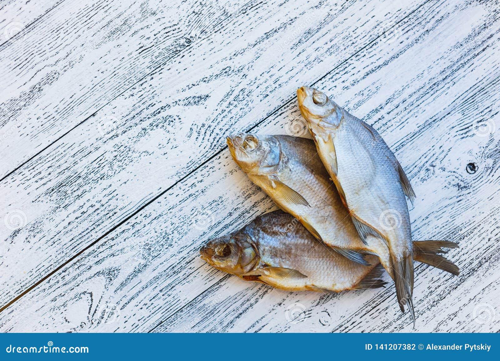 Bugia dell orata di tre pesci essiccati su una tavola di legno leggera