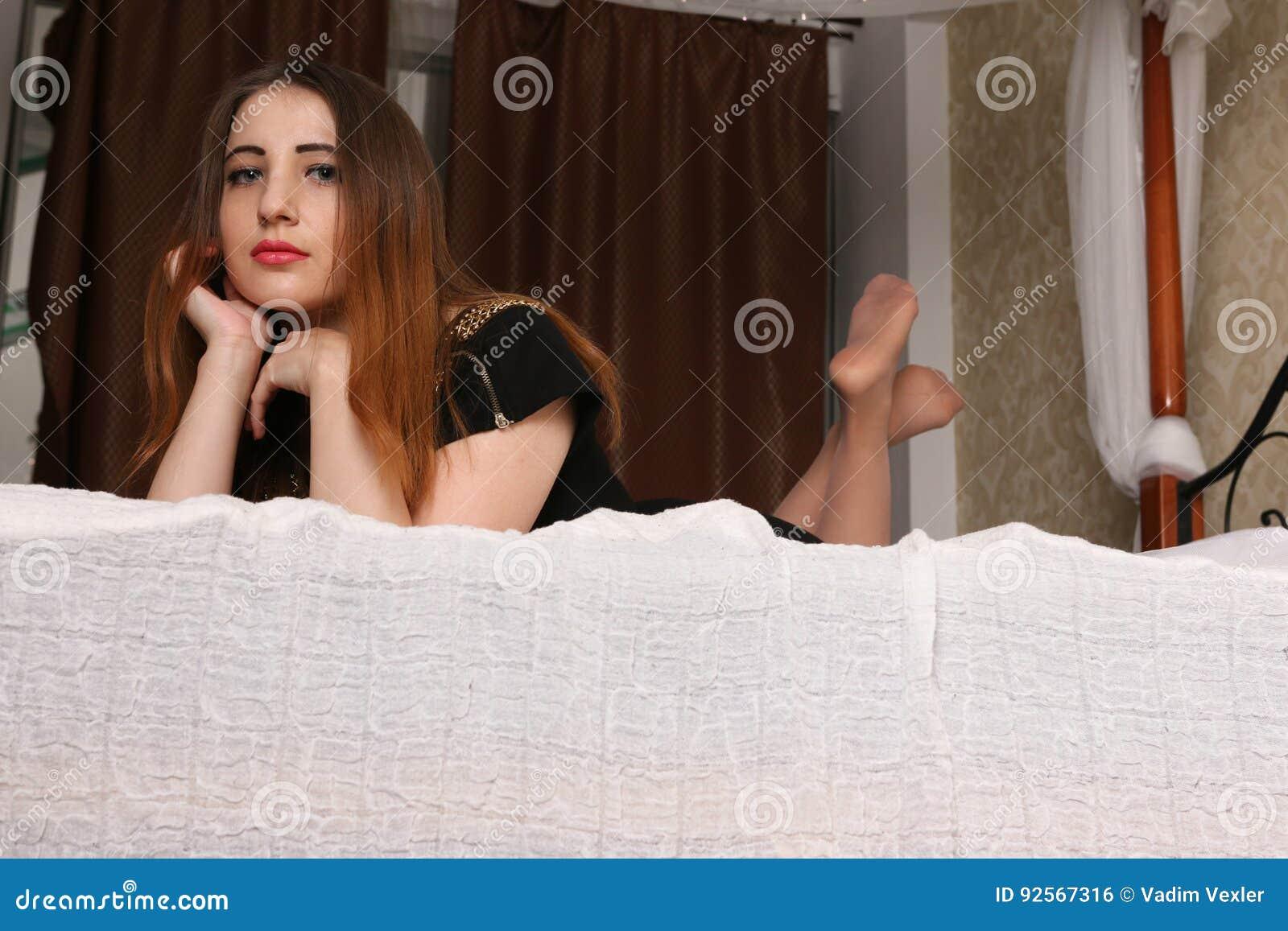 Bugie castane affascinanti sul grande letto e sullo sguardo giù