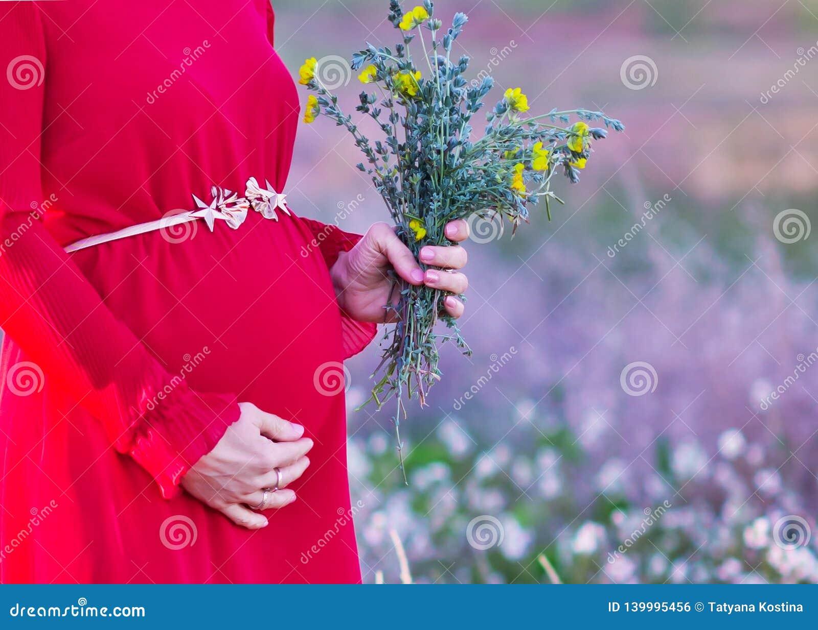 Buik van een zwangere vrouw in een kledingsclose-up
