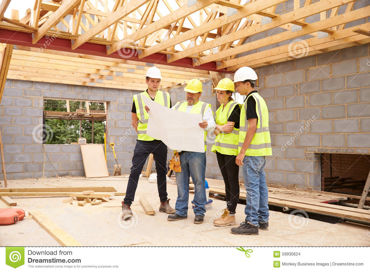 Builder on building site looking at plans with apprentices for House builder online free