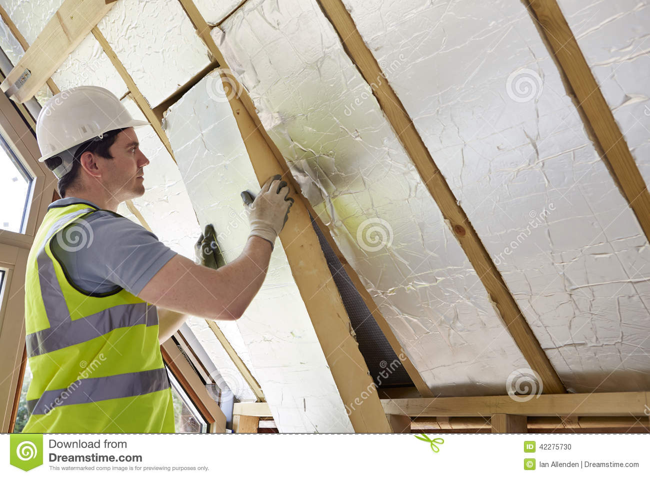 Builder fitting insulation into roof of new home stock for New home insulation