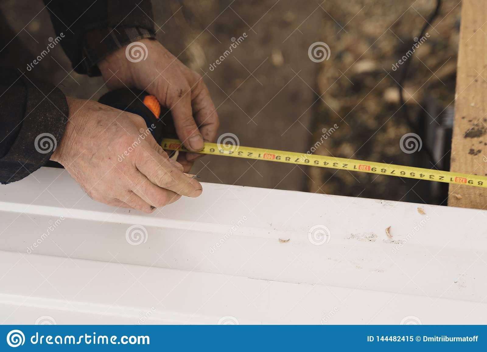 Builder in gloves measures the length of a metal profile with a tape measure.