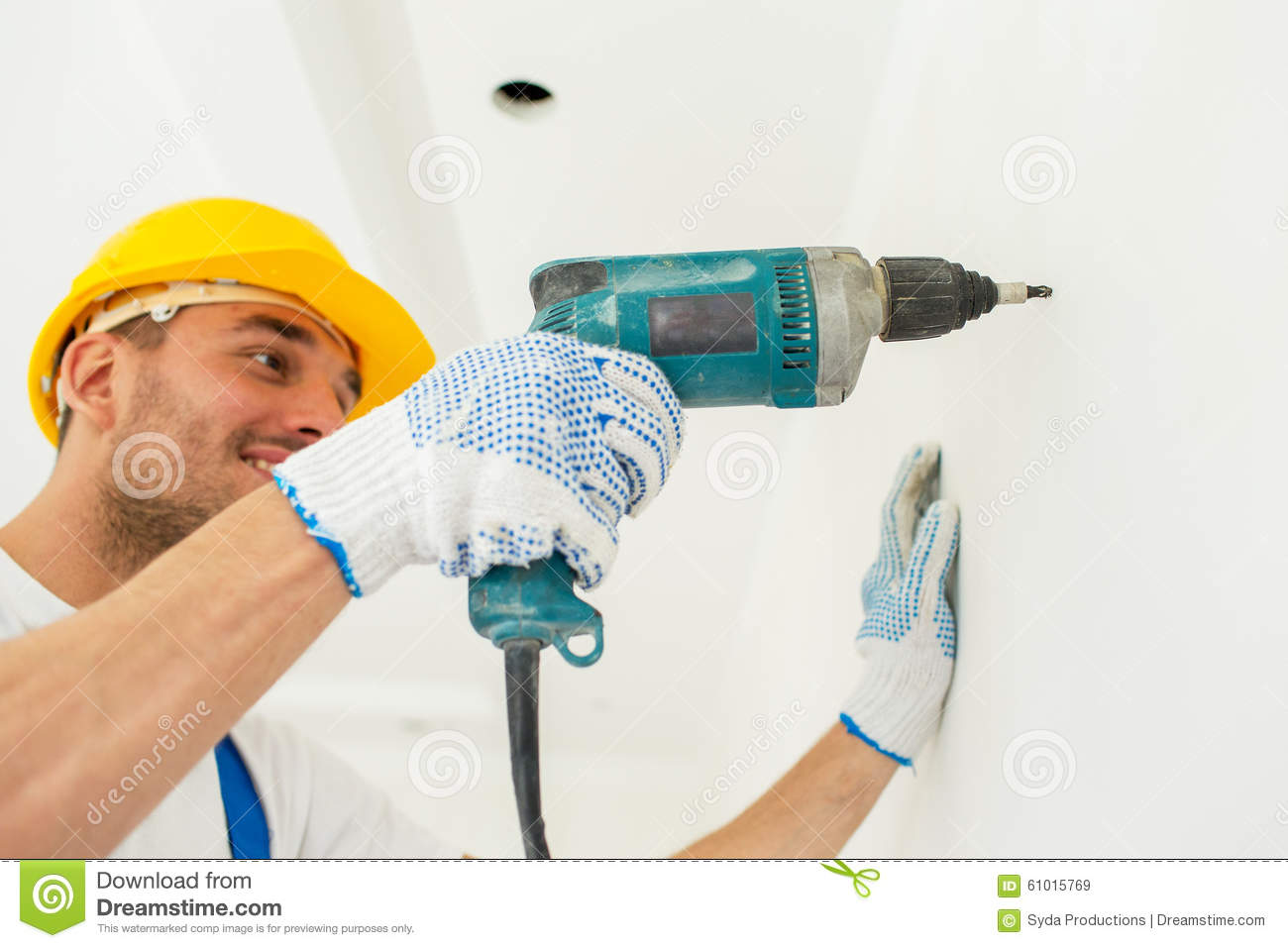 Builder in hardhat with drill perforating wall stock image for Production builder