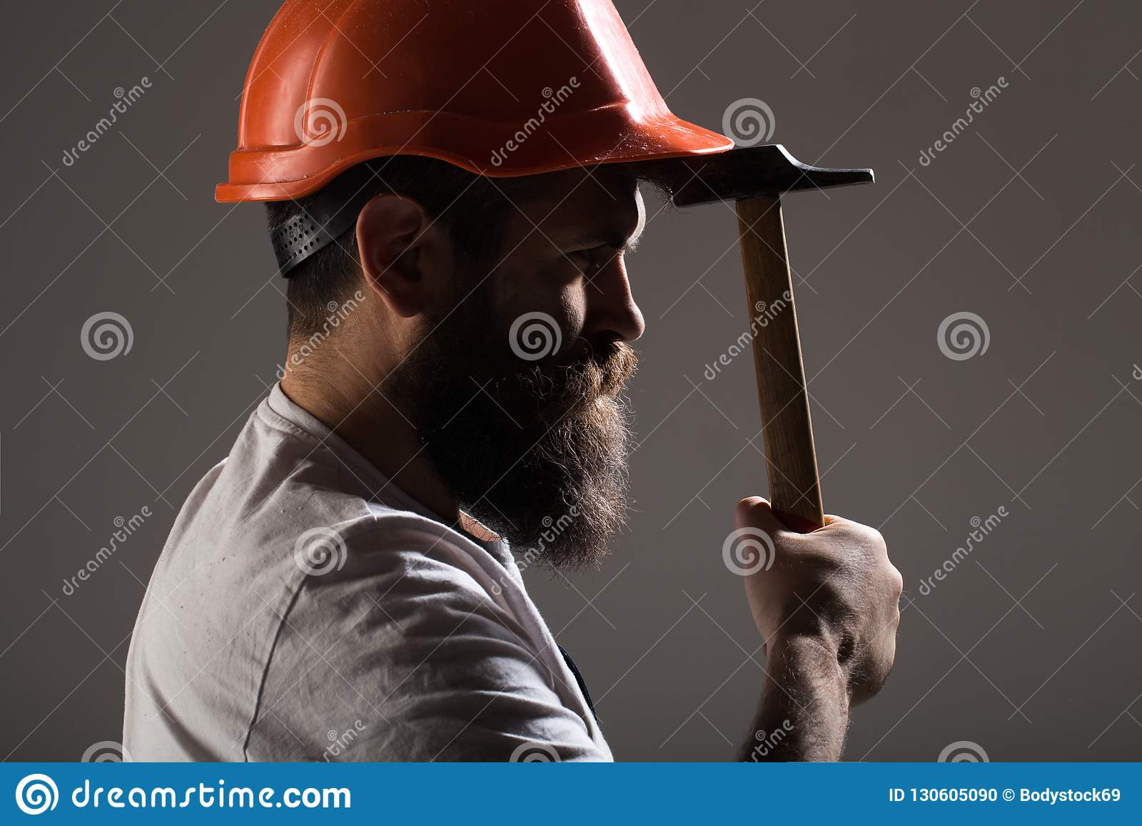 Builder in helmet, hammer, handyman, builders in hardhat. Bearded man worker with beard, building helmet, hard hat