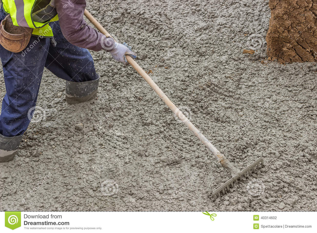 Builder Worker Standing In Fresh Cement Using A Metal