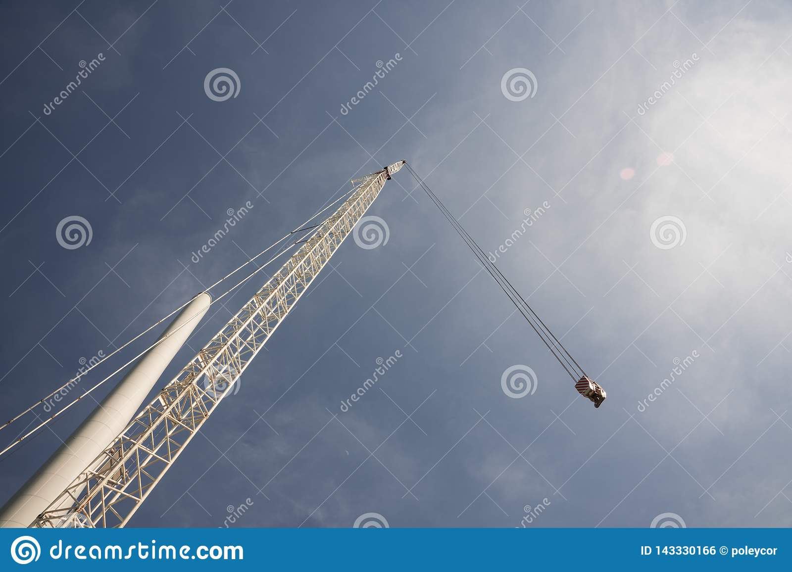 Crane and pole of windmill, against blue sunny sky
