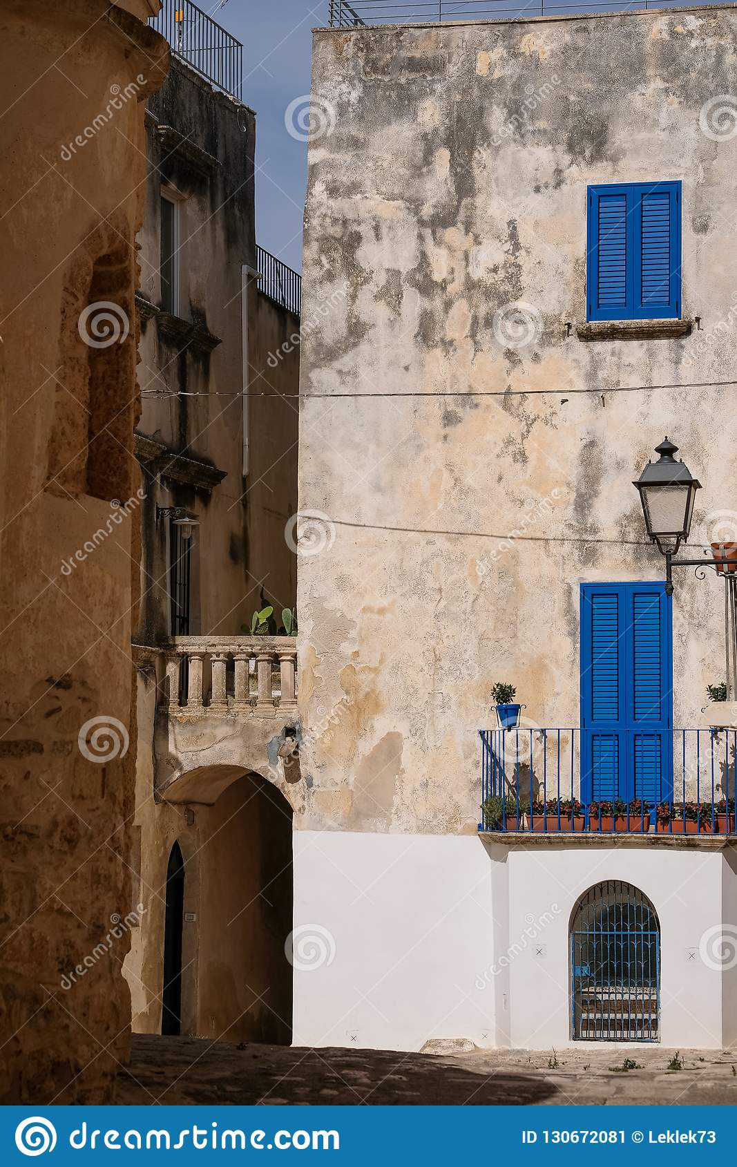 Building with blue shutters on a street in the coastal town of Otranto on the Salento peninsula, Puglia, South Italy.