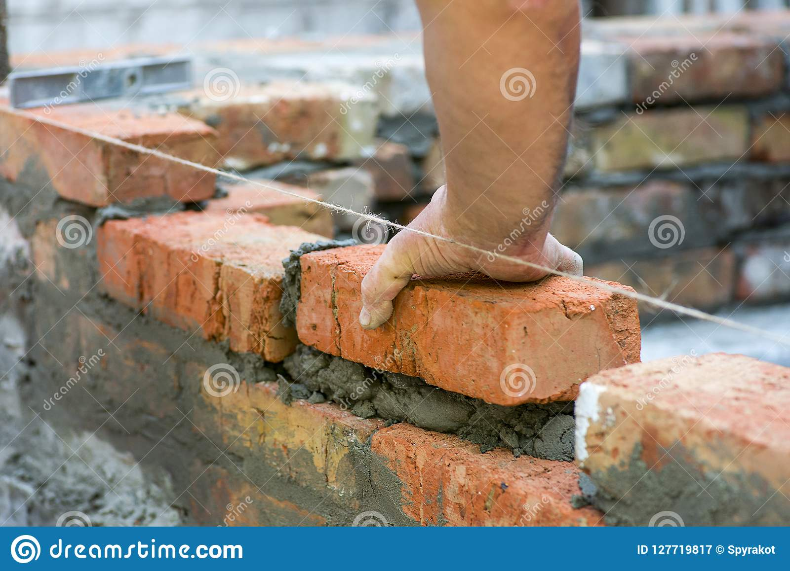 Building brick block wall on construction plant. Worker builds a brick wall in the house. Construction worker laying bricks on ext