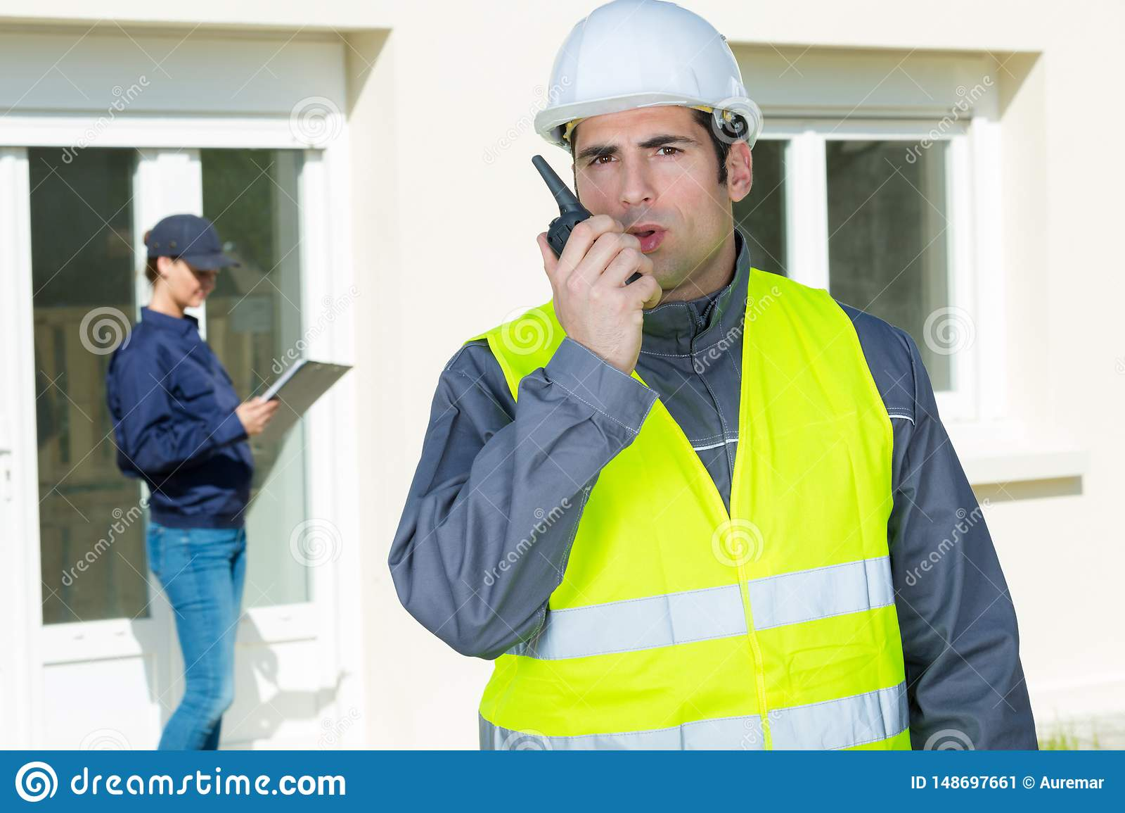 Building construction foreman giving order through walkietalkie