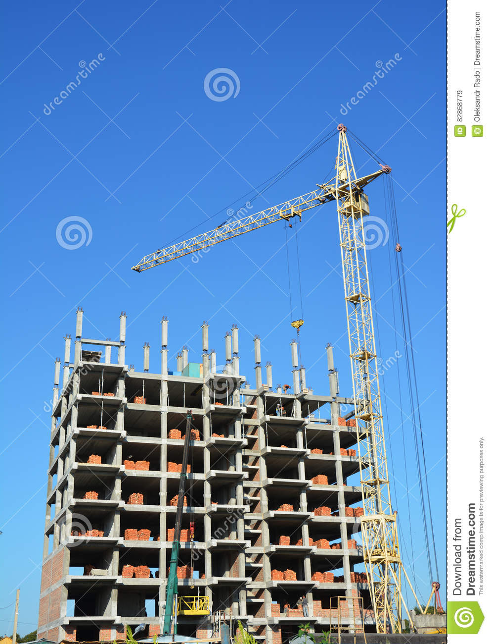 building cranes on construction site with builders building high