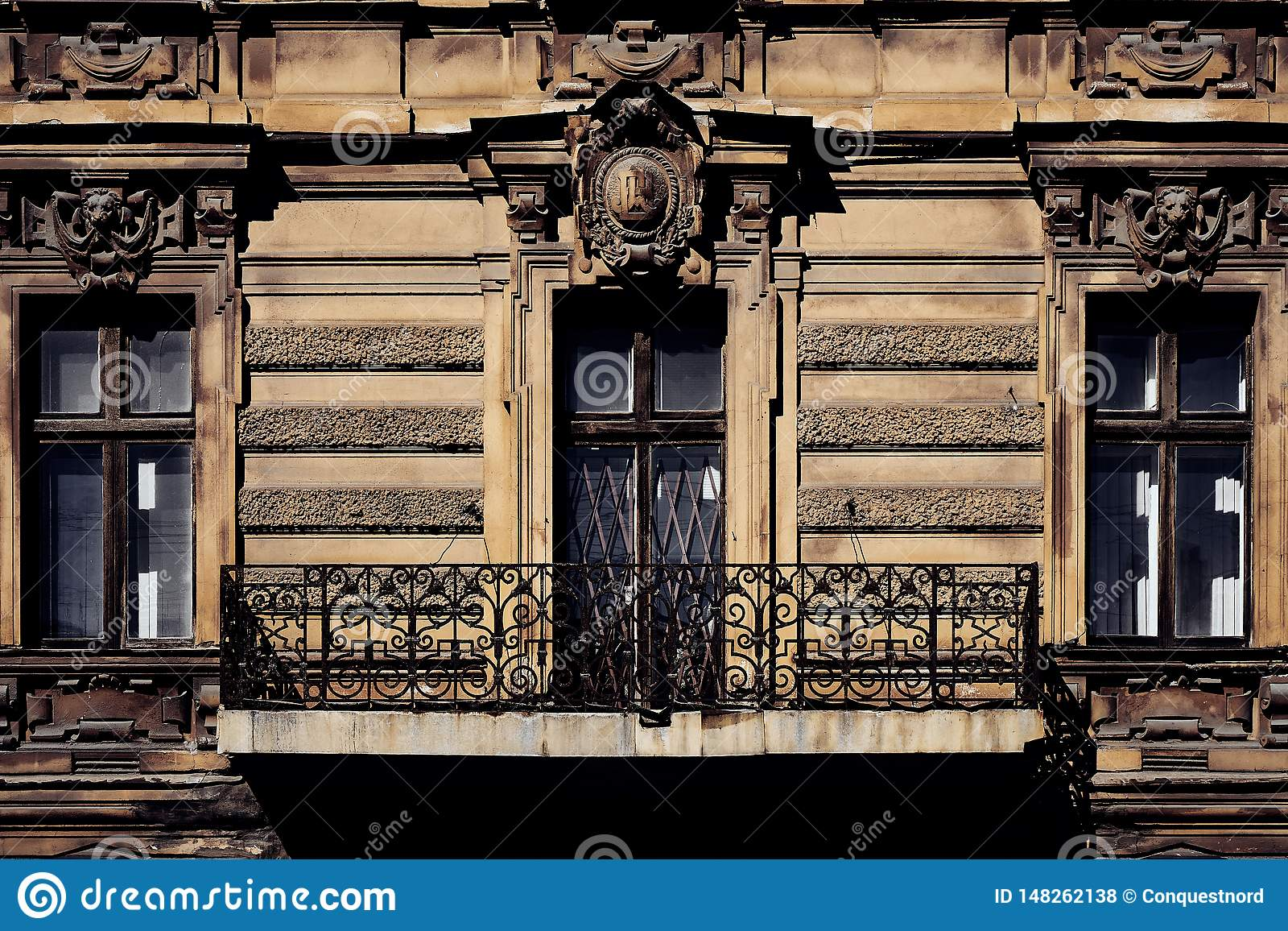 Building facade of old historic house with classic antique arch window and cozy balcony