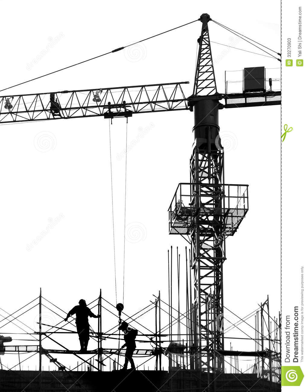 Construction site with crane and scaffolding seen as a silhouette.