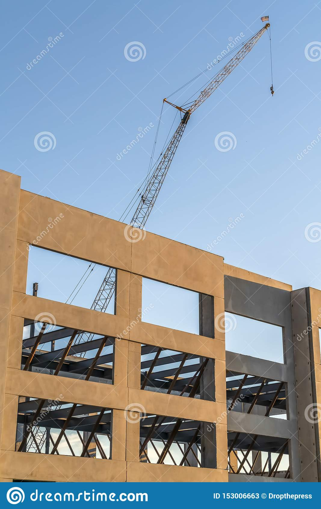 Building under construction with metal crane and blue sky background