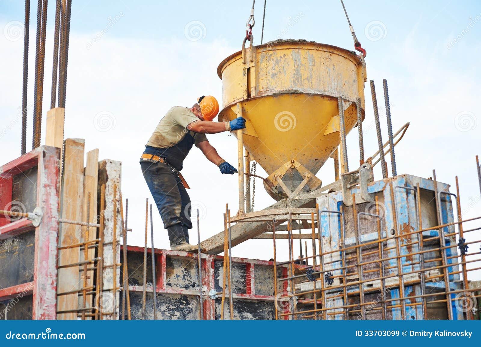 Concrete Building Construction : Building workers pouring concrete with barrel stock image