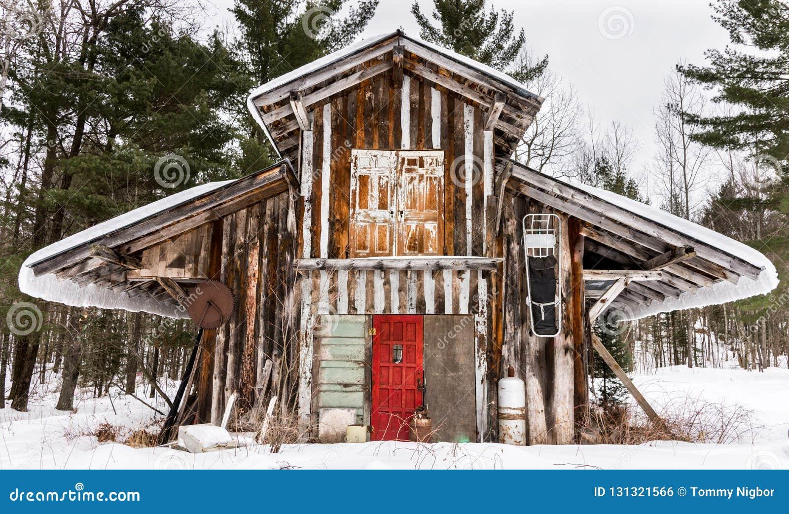 Builing do anjo do inverno da serração coberto em portas brilhantes do coloerd da neve