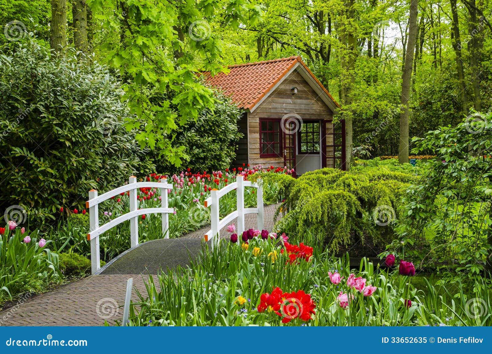 Buitenhuis en witte brug in keukenhof tuinen stock for Jardines exteriores de casas de campo