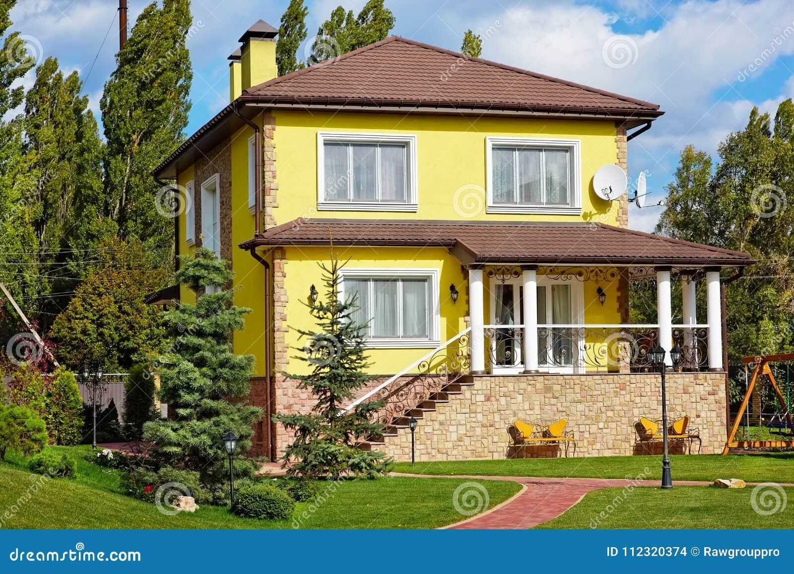 Buitenkant van mooi huis met groene werf en tuin stock foto