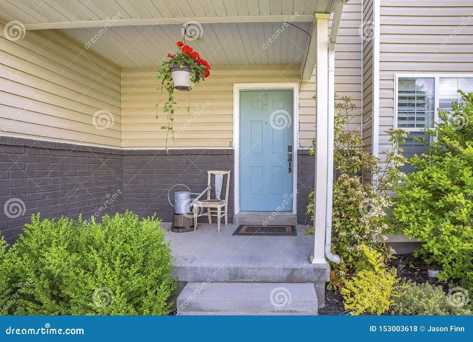 Buitenmening van een huis met stepas en portiek voor de pastelkleur blauwe deur