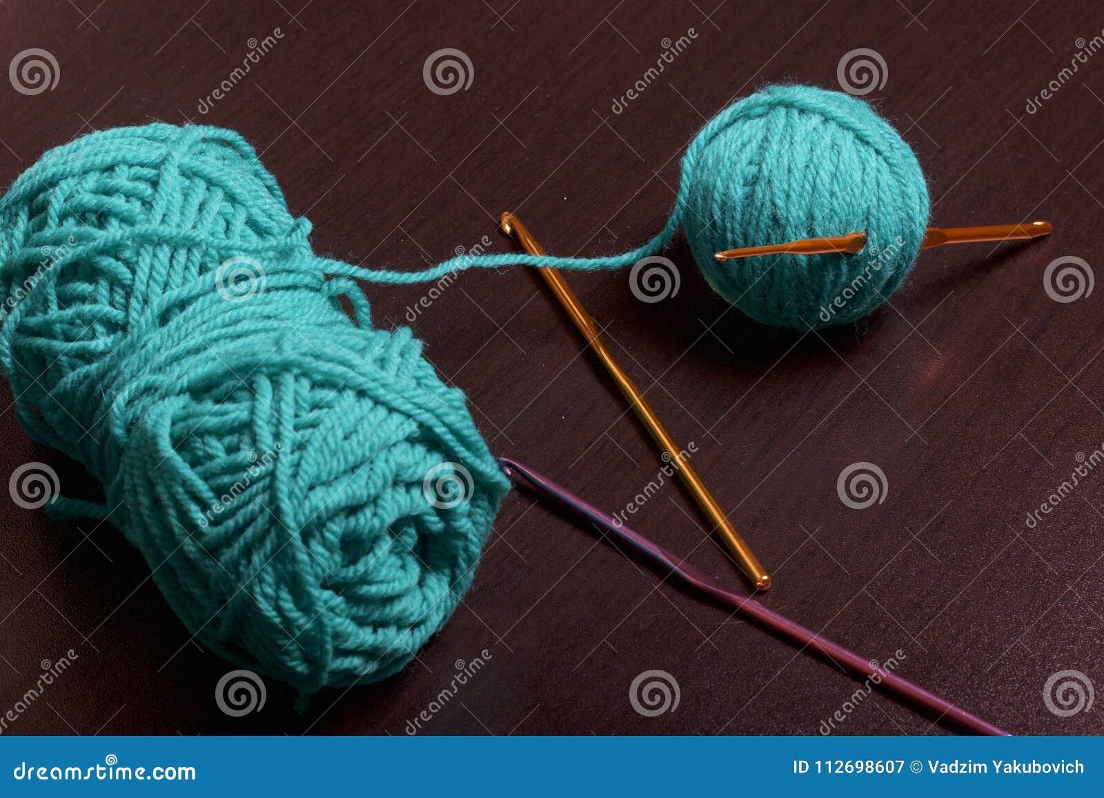 Buizen van draad voor het breien smaragdgroene kleur en haken voor het breien op een donkere achtergrond