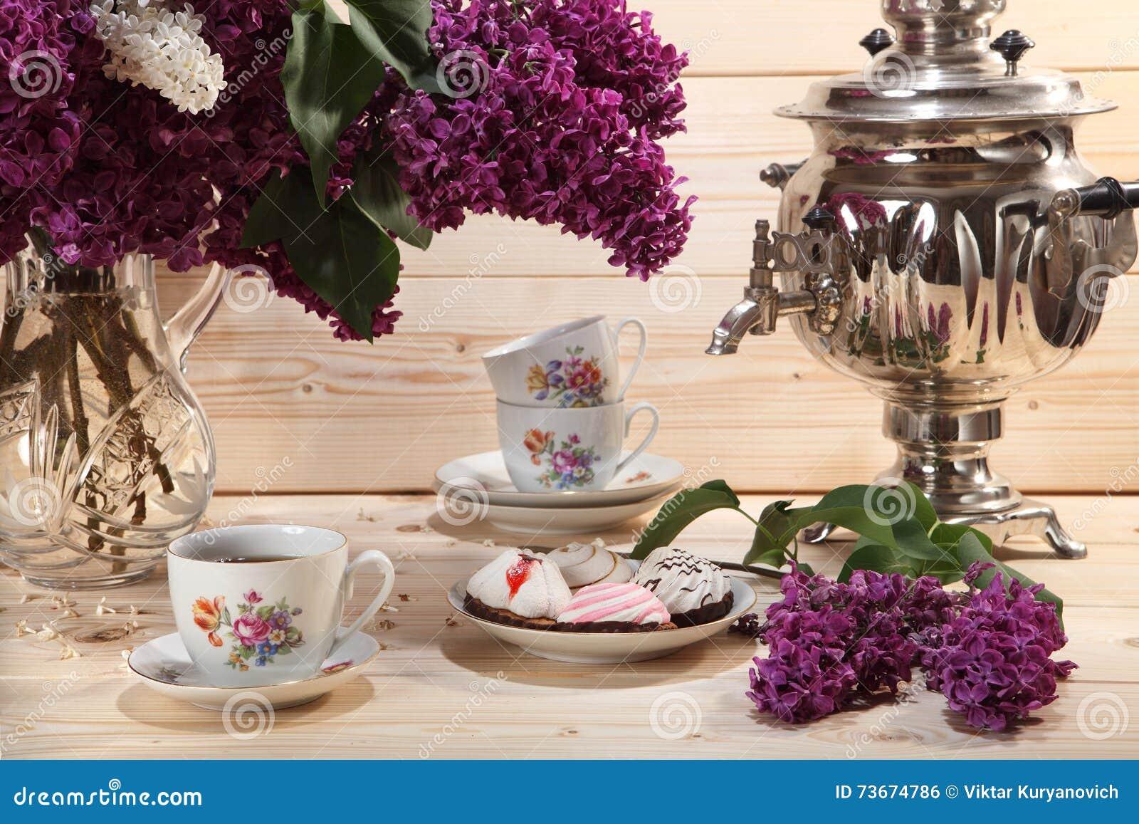 Bukett av lilor, samovar, kopp te och kexet på träbac