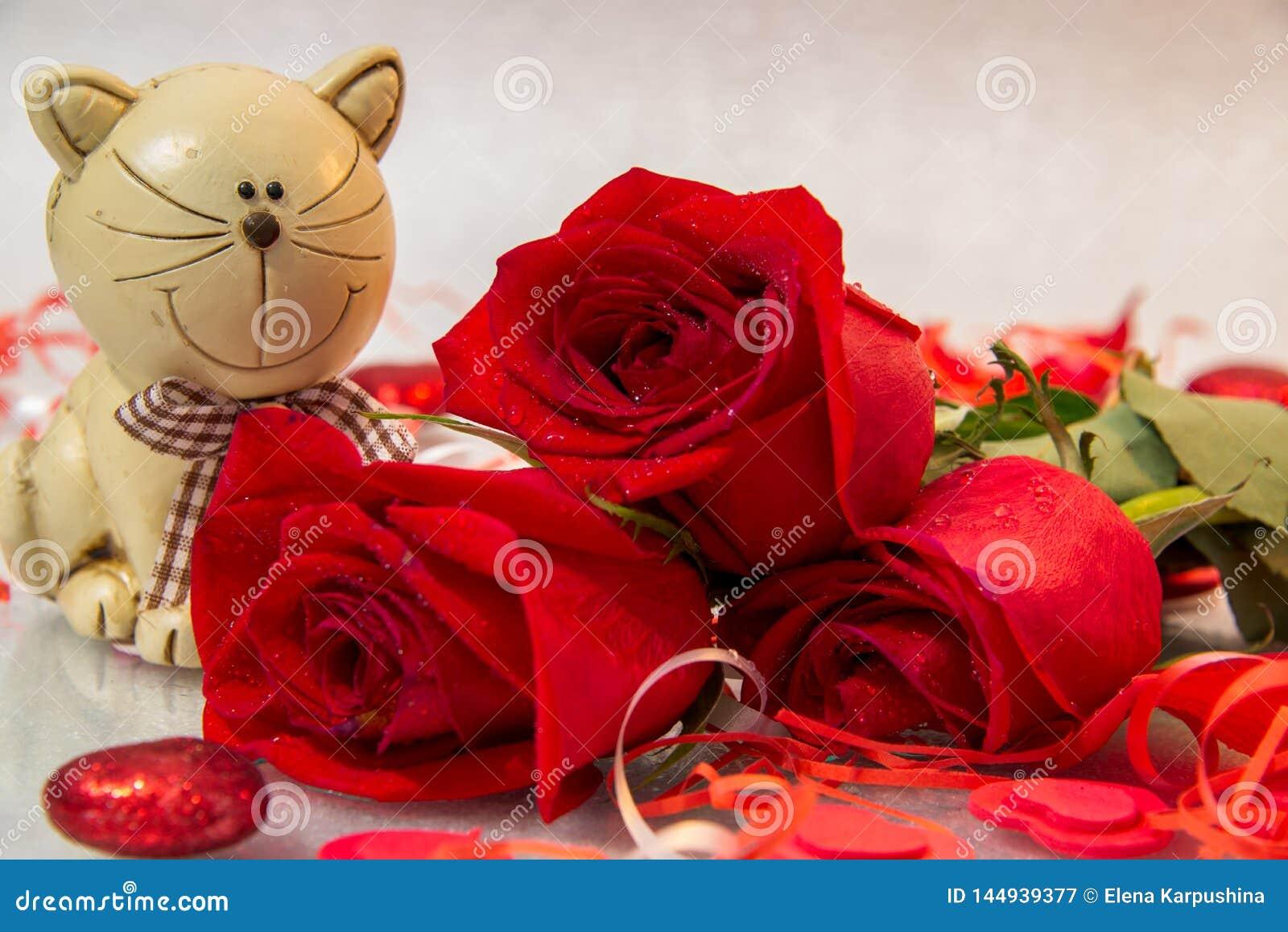 Bukett av röda rosor med en kattstatyett