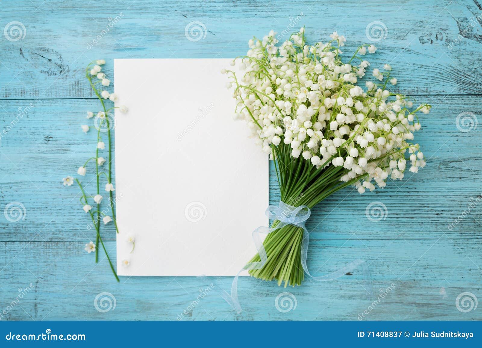 Buketten av blommaliljekonvaljen och tömmer det pappers- arket på den lantliga tabellen för turkos från över, det härliga tappnin