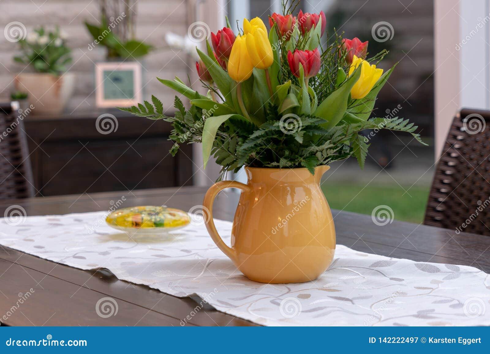 Buketten av färgglade tulpan står i en gul vas