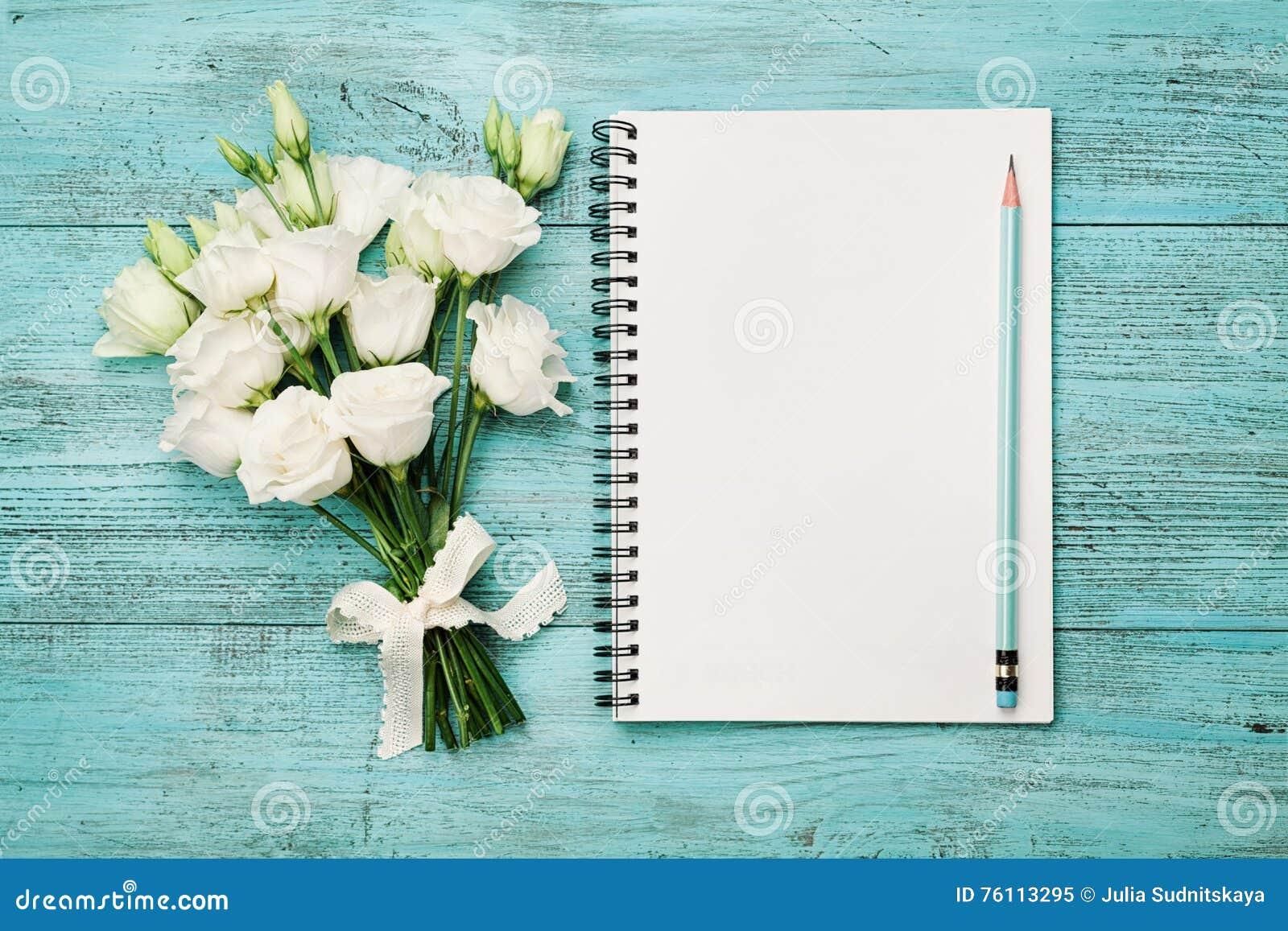 Buketten av vita blommor och tömmer det pappers- arket på den lantliga tabellen för turkos från över Härligt tappningkort, bästa