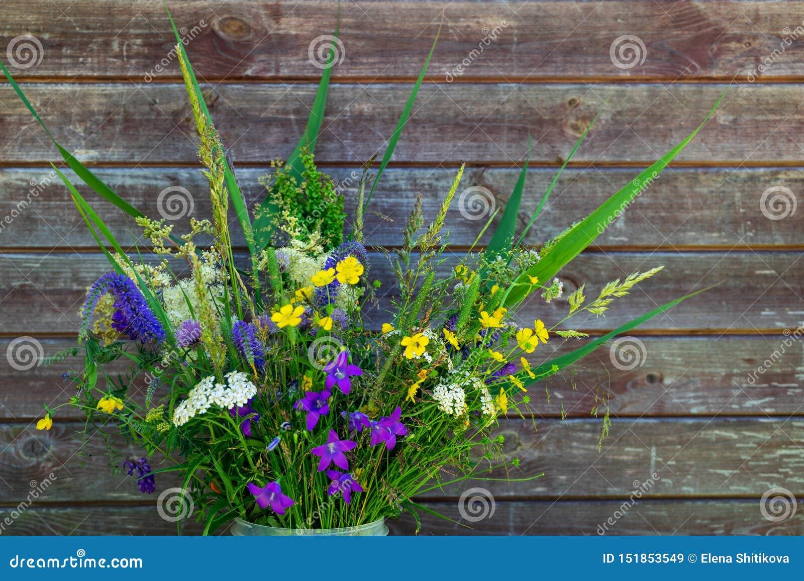 Bukiet dzicy kwiaty na drewnianym ściennym tle Stare deski, rosjanina pole
