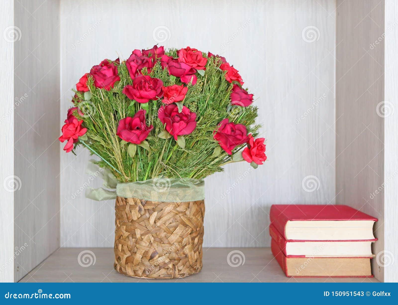 Bukiet sztuczne czerwone róże wewnątrz przetwarza wazę i książki