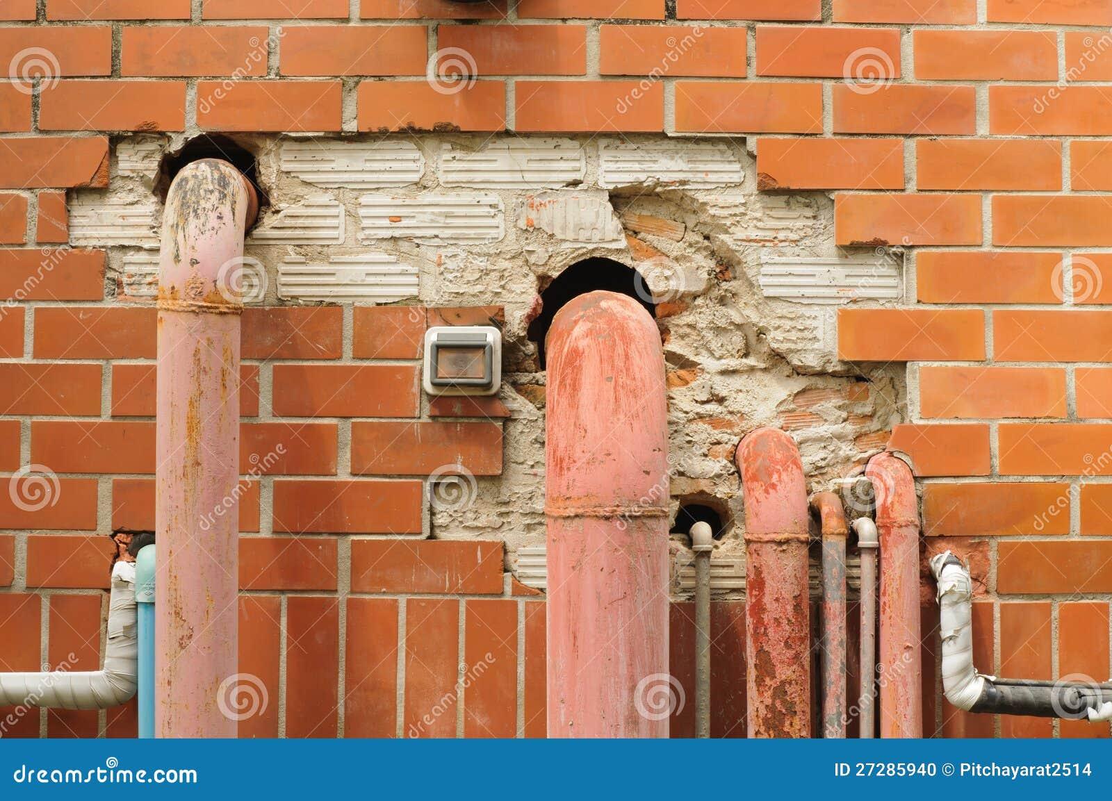 Buktiga rør på en gammal tegelstenvägg